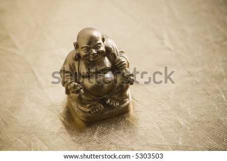 Gold painted buddha figure on a shiny surface.