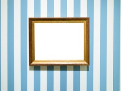 gold painted wooden picture frame with cutout canvas on blue striped wall