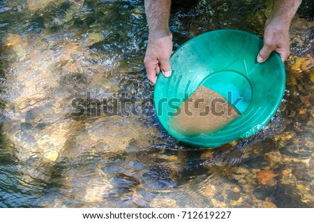 Gold pan filled with mineral rich material. Prospecting for gold and gemstones. Fun and adventure enjoying recreational outdoor activity.