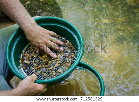 Shutterstock Gold panning and gem mining.  Prospecting tool of classifier used to sift and sort material. Classify mineral rich soil, dirt, pebbles and stones. Prepare soil to pan. Fun, adventure and recreation.
