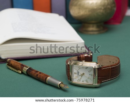gold pen, watch close-ups and an open book on green table