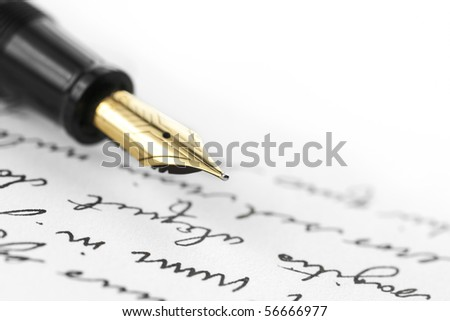 Gold pen with hand written letter. Focus on end tip of fountain pen. #56666977