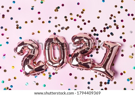 Gold pink balloons in form of numbers 2021 with colorful shiny confetti on pink background. Happy New Year celebration. Flat lay, top view