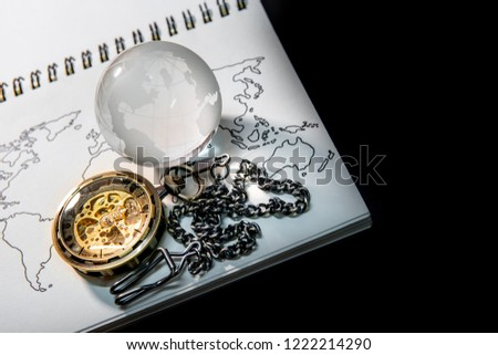 Stock Photo Gold pocket watch and world globe crystal glass on world map outline sketch on paper page of notebook. Travel around the world. Global business concept