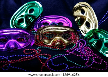 Gold, purple and gold mardi-gras masks with beads on black