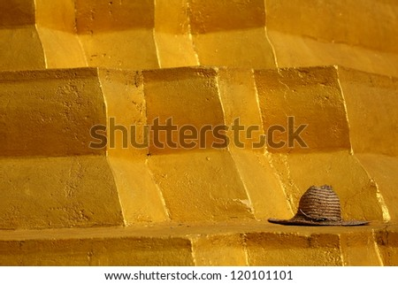 Gold Pyramid. Workers straw hat left on top of a golden structure at a Buddhist temple.