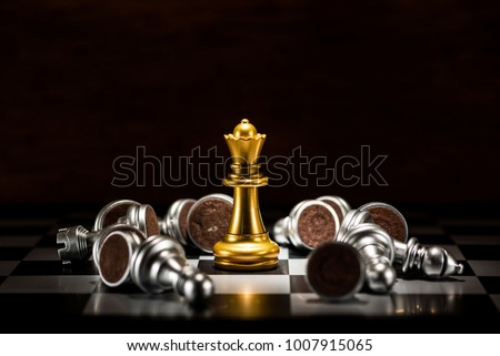 Photo of  gold queen chess surrounded by a number of fallen silver chess pieces , business strategy concept