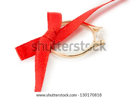 gold ring and a red ribbon with a bow