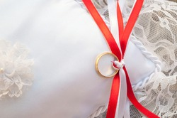 Gold ring placed on a white cloth cushion. Close up view of wedding ring on cushion secured with red and white bow on wedding day.