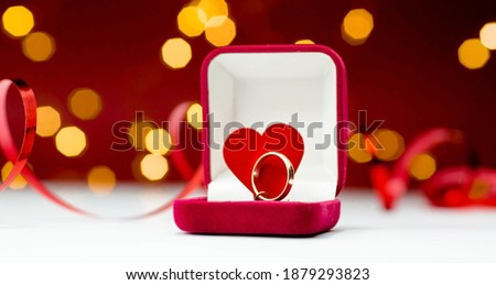 Photo of  Gold ring, wedding ring in red box and, red heart on white-red background with beautiful bokeh. The moment of a wedding, anniversary, engagement, or Valentine's Day. Happy day.