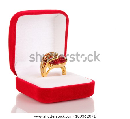 Gold ring with big red gem and clear crystals in red velvet box isolated on white