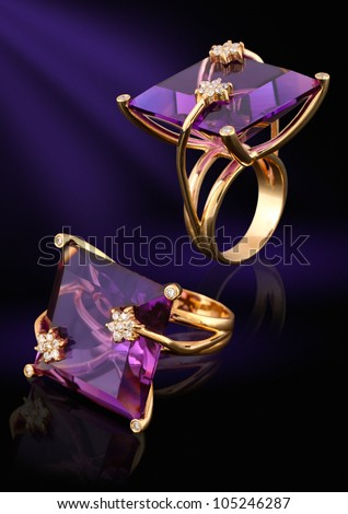 Gold ring with gem and diamonds on dark background