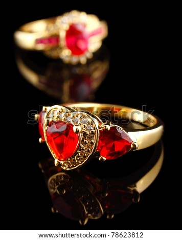 Gold rings with diamonds, on black with reflection