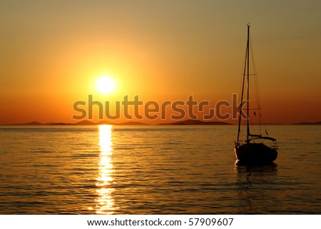 Gold romantic sunset with silhouette of yacht
