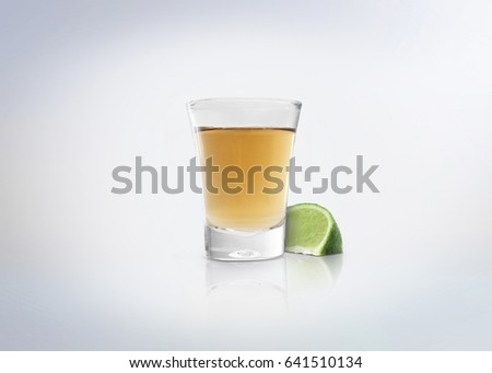 Gold shot of tequila. Alcoholic distilled beverage with slice of lemon / lime on the side. Isolated on white background. #641510134