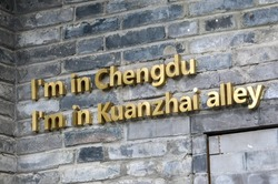 Gold sign saying 'I'm in Chengdu, I'm in Kuanzhai Alley' on brick wall at the the famous Kuanzhai Alley (Wide and Narrow Alleys) in Chengdu, Sichuan, China - three parallel ancient city alleys