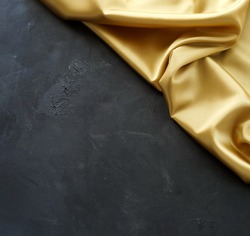 Gold silk fabric texture and black paint textured background . Top view. copy space