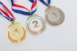 Gold, silver and bronze bronze medals of first, second and third classified, on white background. Victory concept