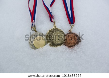Gold, silver and bronze medals for winners in winter games, championships or tournaments , in snow white background  #1018658299