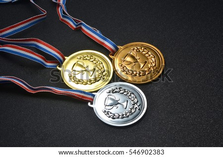 Gold, silver and bronze medals on top of black board #546902383