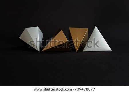 Gold silver minimalistic design geometric solid figures on black. Elegant prism pyramid triangle shape solid objects, paper background.