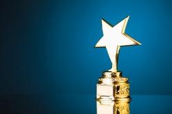 gold star trophy award against blue background