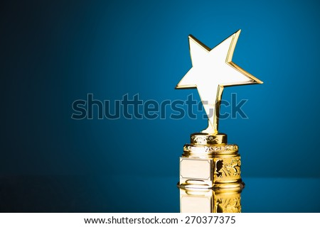 gold star trophy award against blue background