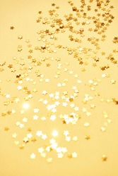 Gold stars background. Yellow glitter backdrop. Golden texture. New year luxury snow. Copyspace. Shimmer confetti wallpaper. Dreamy shiny design detail