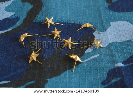 Gold stars for shoulder straps on blue camouflage fabric. Military emblems of Russian troops and services. No people #1419460109