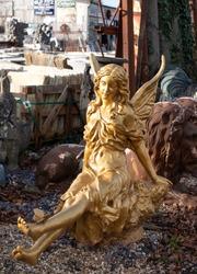 Gold statue amidst other ephemera at reclamation yard. Photographed November 2020.