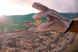 gold stone held by a miner, with the background of an industrial mining company. Large open pit miner in the Atacama Desert, chile.