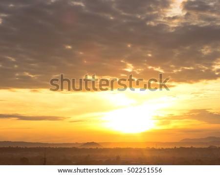 gold sun rise under gray cloudy upper sea in rain season  #502251556