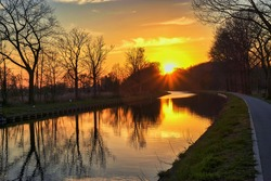 Gold sunset over river with sun rays, tree silhouettes and reflection on water. High quality photo