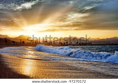 Gold sunset with mountains and big wave