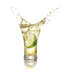 gold tequila shot with splash isolated on white background. Lime is falling in the alcohol drink