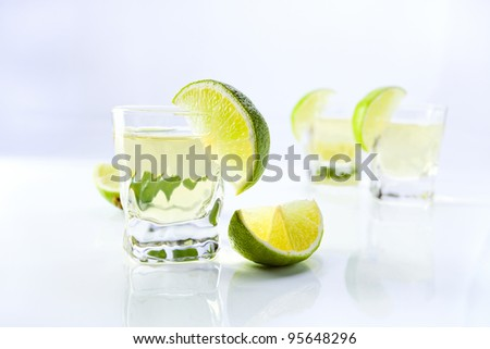 gold tequila with lime on a white reflective background.