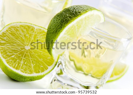 gold tequila with lime on a white reflective background .