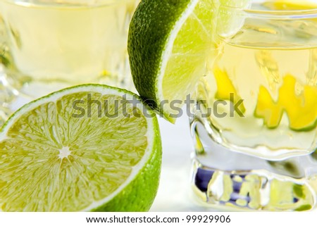 gold tequila with lime on a white reflective background , focus on a lime. - stock photo