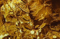 Gold texture. Rough structure mineral. Rock texture. Gold Ore. Gold rocks. Stone background.