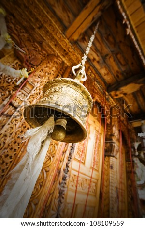 gold tibetan bell near old temple