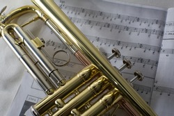 Gold trumpet laying on musical sheet