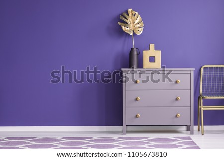 Gold vase on violet cabinet next to a chair in purple living room interior with patterned carpet