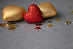 Gold volumetric hearts and a red heart from glitter on a gray background with candies.