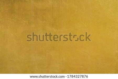 Gold wall texture background. Yellow shiny gold foil paint on wall surface with light reflection, vibrant golden luxury wallpaper  Foto d'archivio ©