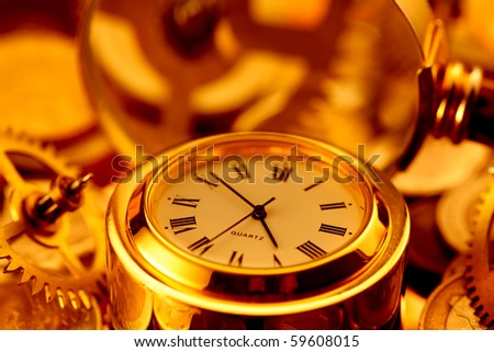 gold watches, coins, gears and magnifying glass on the mirror surface