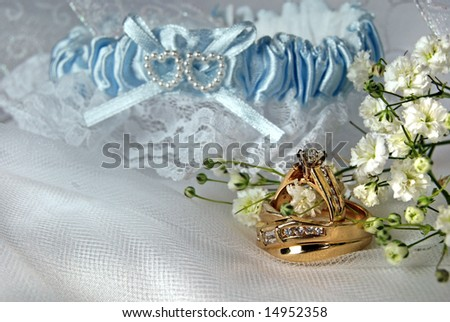 gold wedding rings and garter on tulle