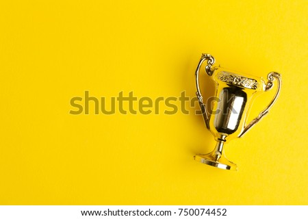 Gold winners achievement trophy on a yellow background #750074452