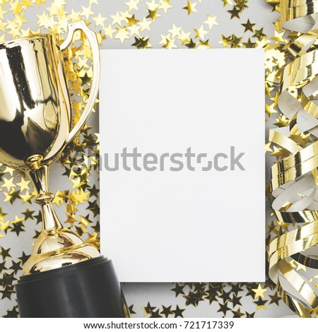 Gold winners trophy with a blank poster label and golden shiny stars #721717339