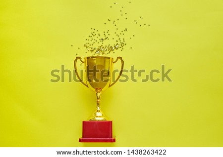 Gold winners trophy with golden shiny stars on yellow background #1438263422