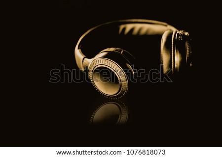 Gold Wireless Headphones on a black background Gold dark tone style.